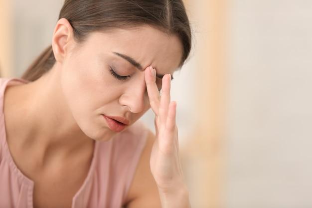 Frau, die unter kopfschmerzen drinnen leidet