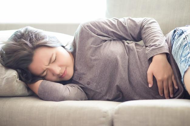 Frau, die unter magenschmerzen auf sofa leidet