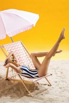 Frau, die unter regenschirm am schönen strand sonnenbaden und moment genießen