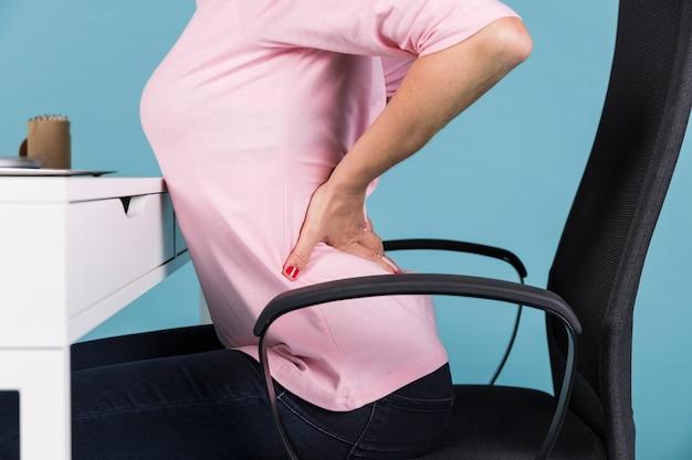 Frau, die unter rückenschmerz beim sitzen auf stuhl leidet