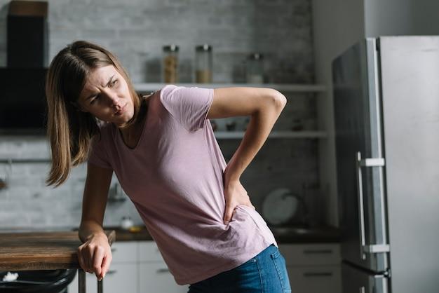 Frau, die unter rückenschmerzen leidet