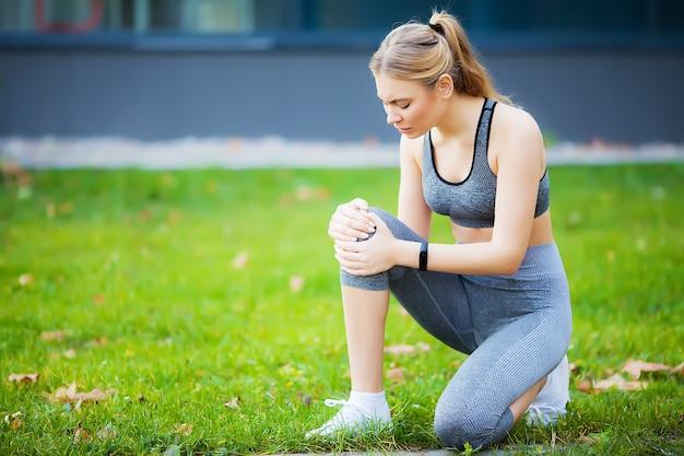 Frau, die unter schmerzen im bein nach dem training leidet