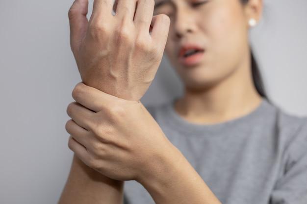 Frau, die unter schmerzen im handgelenk leidet.