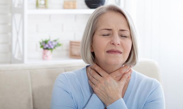 Frau, die unter stress oder kopfschmerzen leidet und vor schmerz verzog das gesicht, während sie ihren nacken hält