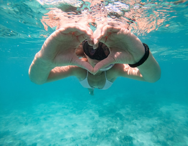 Frau, die unter wasser schwimmt. konzept über urlaub und natur
