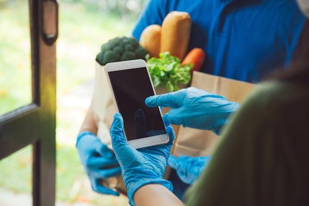 Frau, die unterschrift im digitalen mobiltelefon anhängt, nachdem lebensmittelgeschäft-liefermann lebensmittel liefert