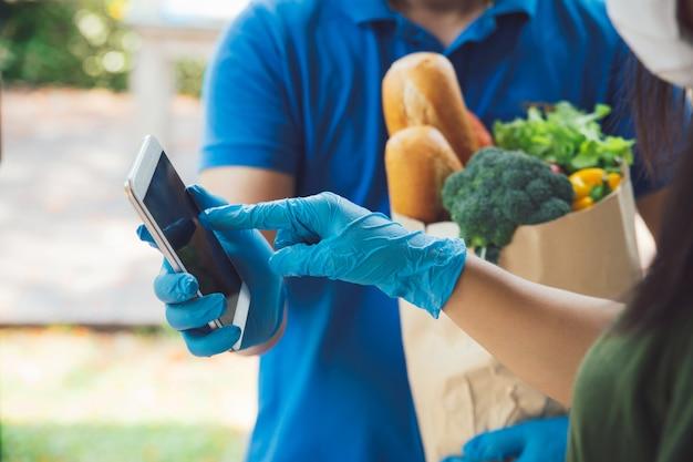 Frau, die unterschrift im digitalen mobiltelefon nach lebensmittelgeschäft anhängt, das einer frau lebensmittel liefert