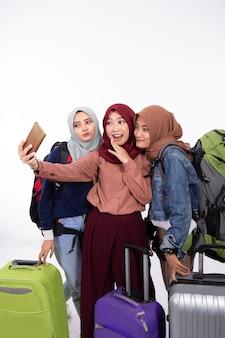 Frau, die urlaub hält und koffer nimmt, macht selfie