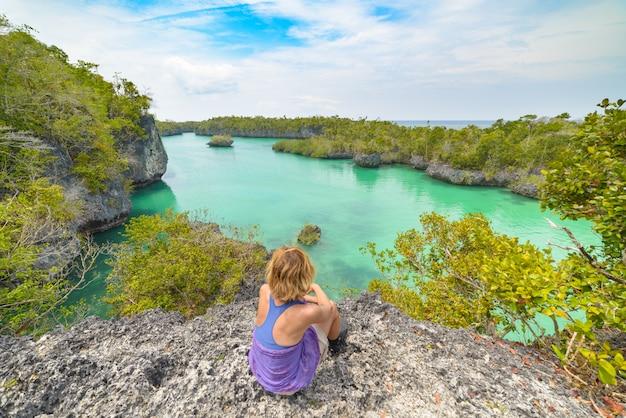 Frau, die ursprünglichen küstenlinienregenwaldblauen see des tropischen paradieses in bair island betrachtet