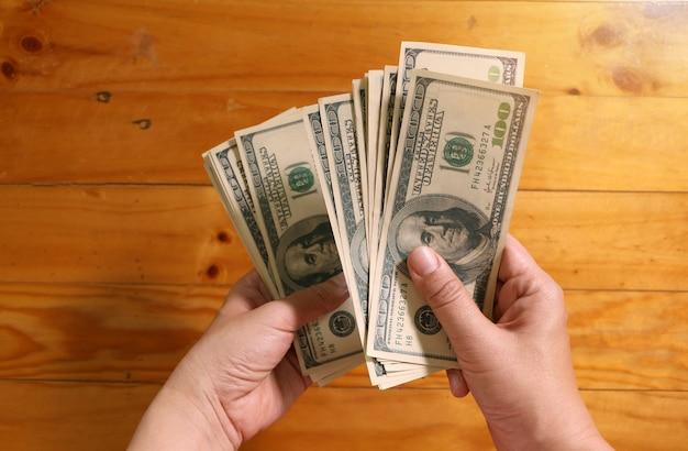 Frau, die us-dollar geldbanknoten hält