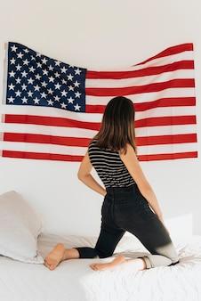 Frau, die us-flagge auf der wand steht auf bett betrachtet