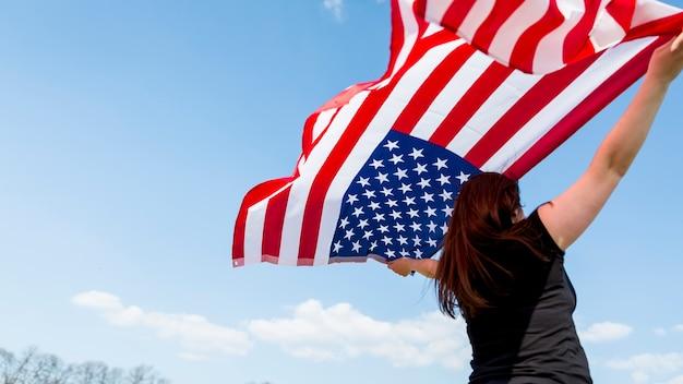 Frau, die usa-flagge während der feier des unabhängigkeitstags wellenartig bewegt