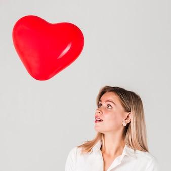 Frau, die valentinsgrußballon betrachtet