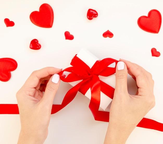 Frau, die valentinsgrußgeschenk einwickelt