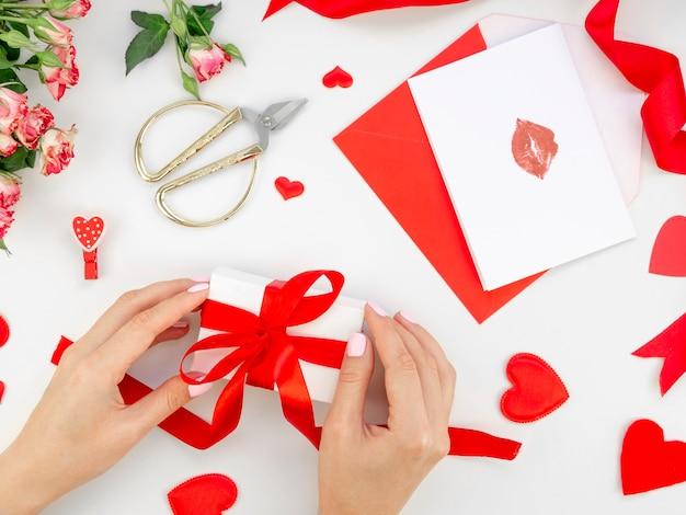 Frau, die valentinsgrußgeschenk vorbereitet