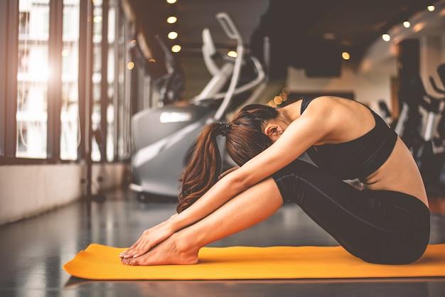 Frau, die verbiegendes yoga tut und unten in den eignungstrainings turnhalle ausrichtend gegenüberstellt