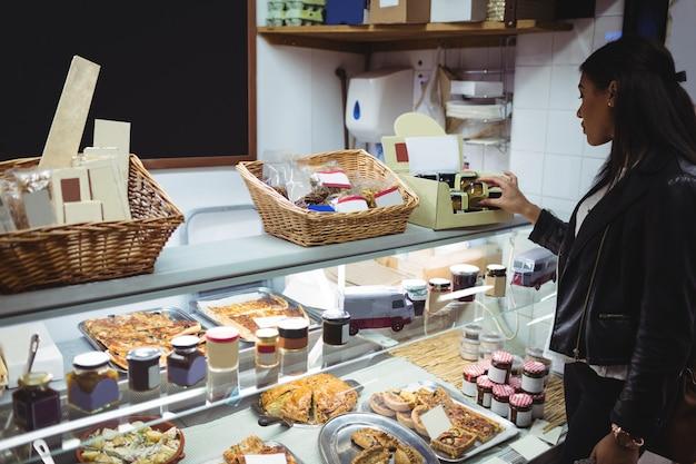 Frau, die verpacktes essen am lebensmittelschalter auswählt