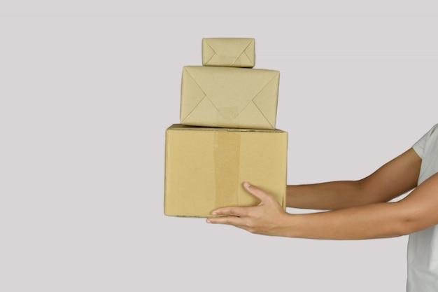 Frau, die verpackungsboxen in den händen auf grauem raum hält.