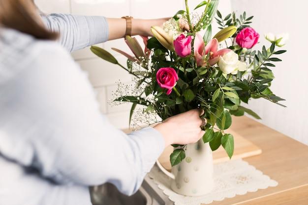 Frau, die verschiedene blumen in einer vase anordnet