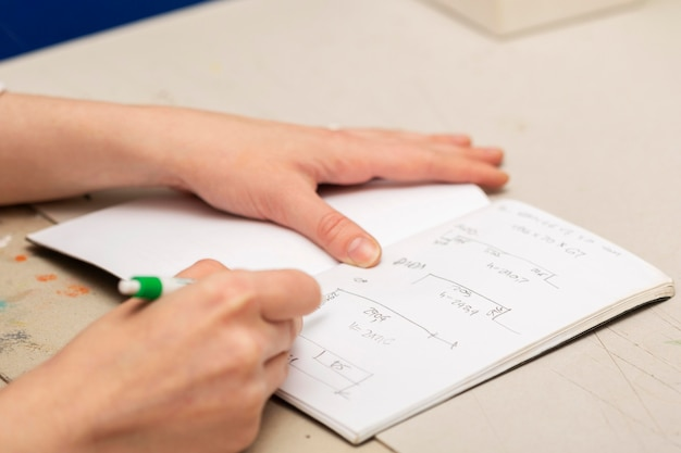 Frau, die verschiedene maße auf ein notizbuch schreibt