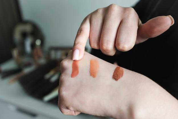 Frau, die verschiedene schattierungen der flüssigen grundierung auf ihrer hand gegen nahaufnahme prüft