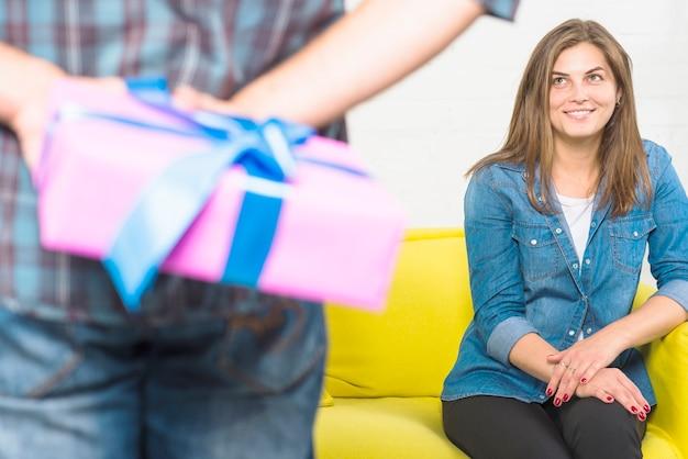 Frau, die versteckendes valentinsgrußgeschenk des freundes hinter seinem zurück betrachtet