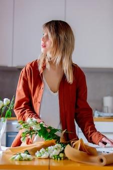 Frau, die versucht, als floristengeschäftsfrau zu arbeiten und rosafarbenen blumenstrauß einzuwickeln