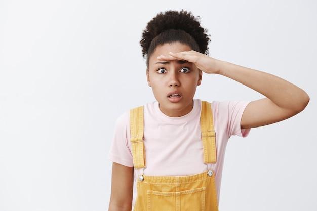 Frau, die versucht, durch kranken nebel zu sehen. porträt eines besorgten und verwirrten attraktiven afroamerikaners in gelben latzhosen, die handfläche nahe stirn halten und weit weg starren, über grauer wand stehend