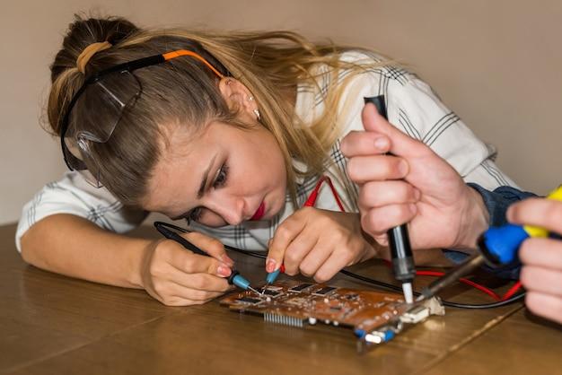 Frau, die versucht, problem im motherboard des computers zu finden