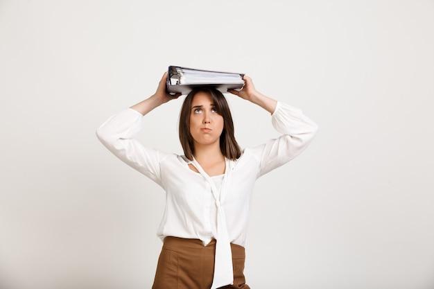 Frau, die versucht, stapel von dokumenten auf kopf zu halten