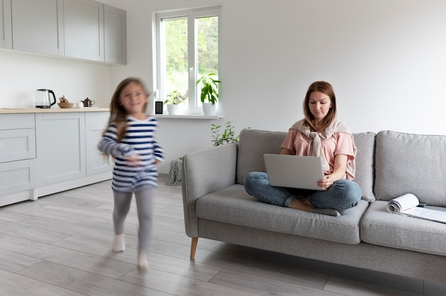 Frau, die versucht, von zu hause aus am laptop zu arbeiten, während ihre kinder herumlaufen