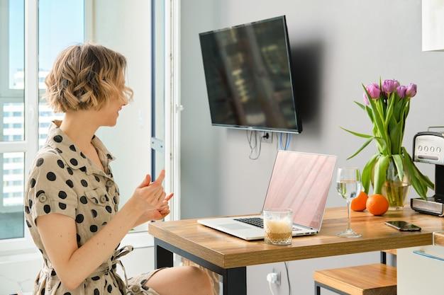 Frau, die videoanruf an geschäftspartner unter verwendung des laptops macht und bildschirm mit virtuellem web-chat betrachtet