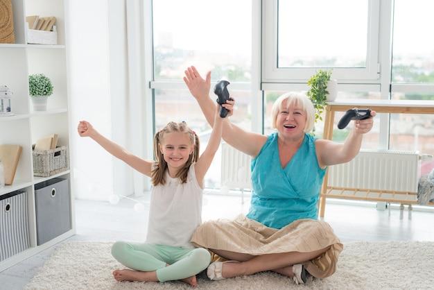Frau, die videospiel mit enkelin spielt
