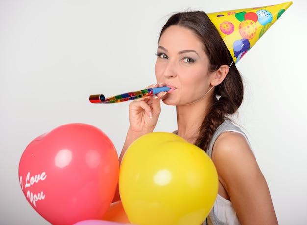 Frau, die viele ballone in herz-förmigem hält.