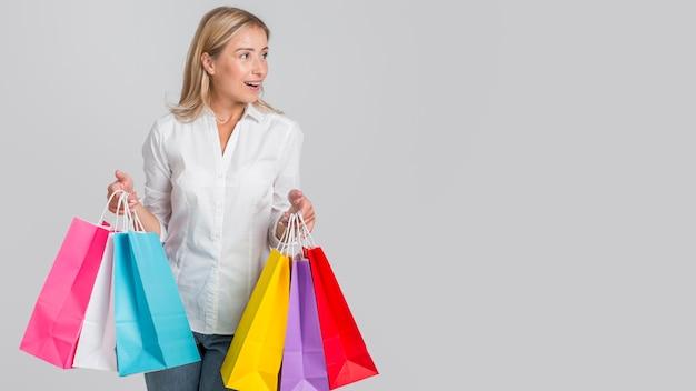 Frau, die viele bunte einkaufstaschen mit kopienraum hält