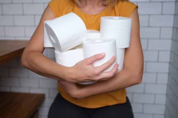 Frau, die viele rollen toilettenpapier im badezimmer hält auswahl von toilettenpapier für das heimkonzept
