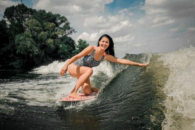 Frau, die viele spritzer durch wakeboard anhebt