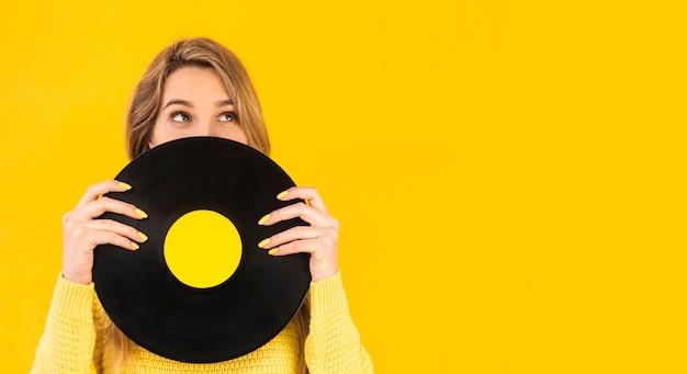 Frau, die vinyl mit kopienraum hält