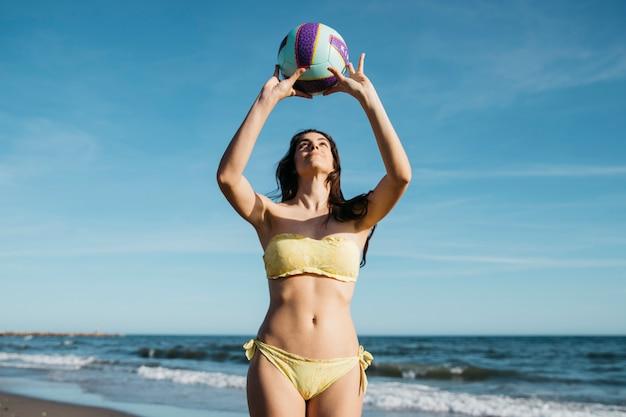 Frau, die volleyball am strand spielt