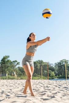 Frau, die volleyball am strand übt