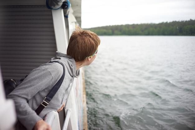 Frau, die vom deck während des reisens durch schiff späht