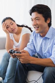 Frau, die vom freund ignoriert wird, der zu hause videospiele im wohnzimmer spielt