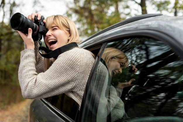 Frau, die von beweglichem auto fotografiert