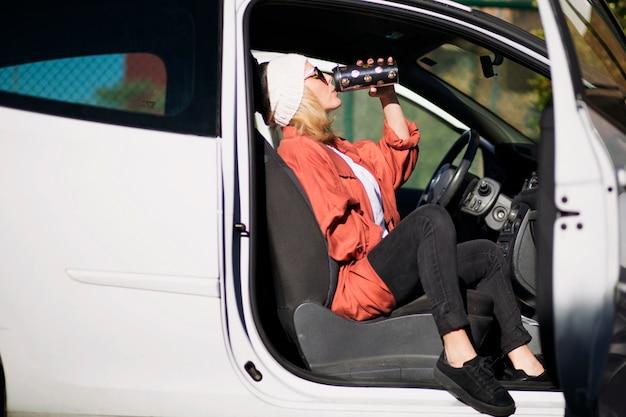 Frau, die von der thermosflasche im auto trinkt