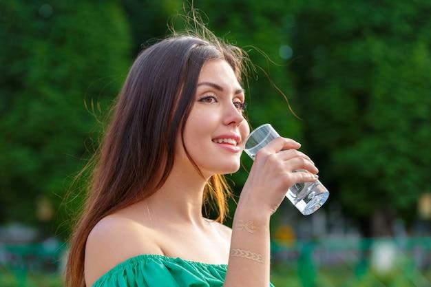 Frau, die von einem glas wasser, gesundheitswesenkonzeptfoto trinkt