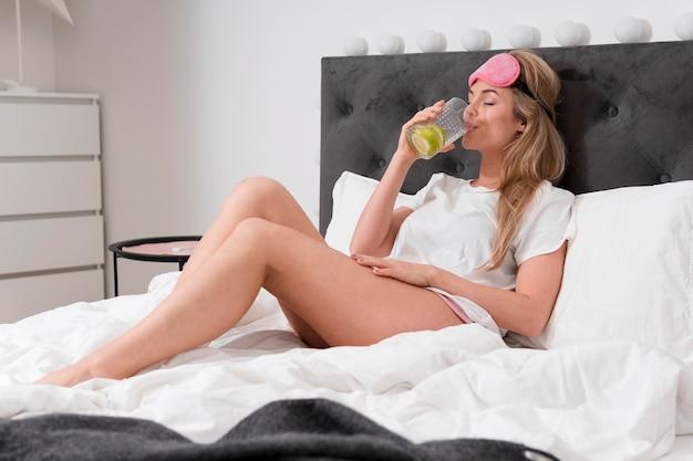 Frau, die von einem glas wasser mit limettenscheiben trinkt