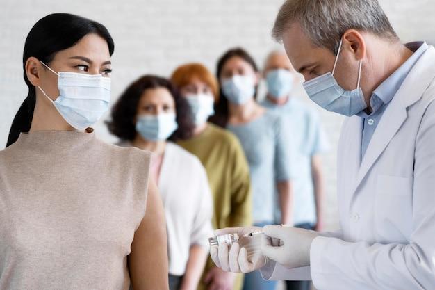 Frau, die von einem männlichen sanitäter mit medizinischer maske geimpft wird