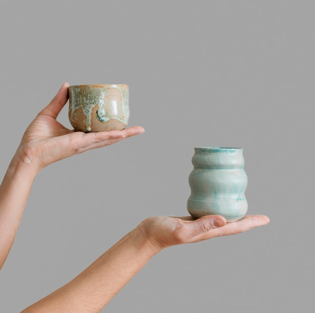 Frau, die von ihr selbst hergestellte keramikstücke hält