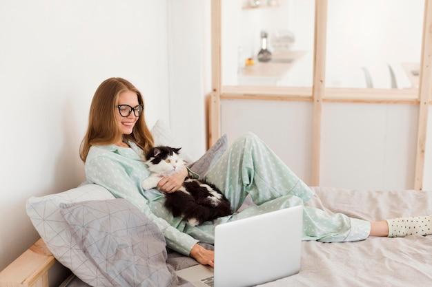 Frau, die von zu hause auf laptop arbeitet, während katze hält