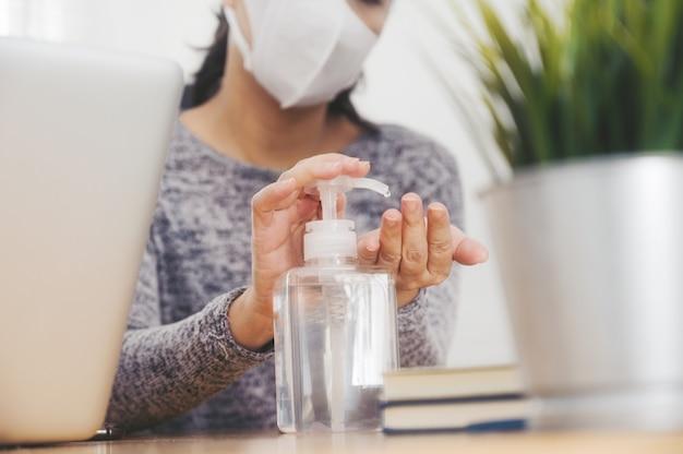 Frau, die von zu hause aus schutzmaske trägt. reinigen sie ihre hände mit desinfektionsgel. büroangestellter in quarantäne. heimarbeit zur vermeidung von viruserkrankungen.